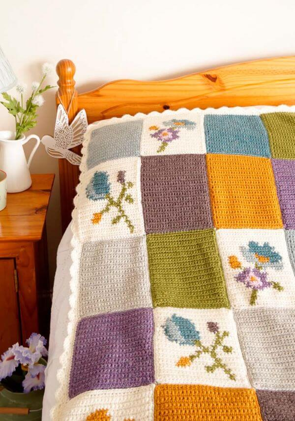 Crochet bed coverlet with flowers in the squares