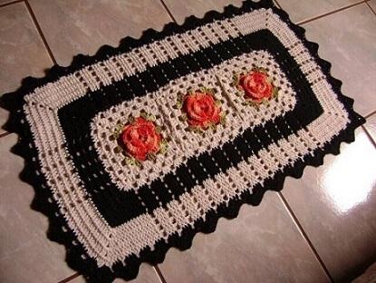 Crochet kitchen rug with orange flowers and black border