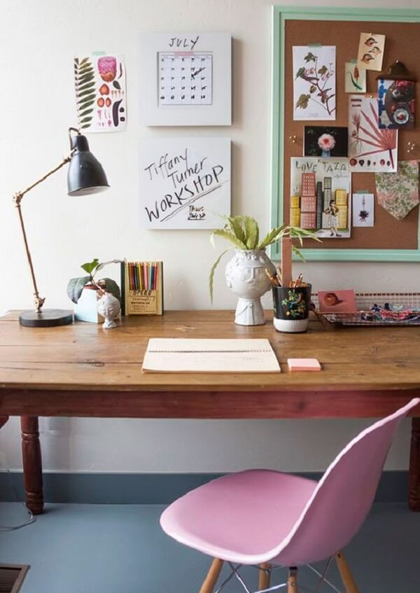 Minimalist decor with wooden table and corkboard on the wall