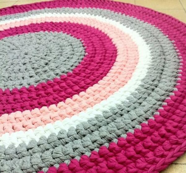 Round crochet rug blending shades of light pink, pink, gray and white