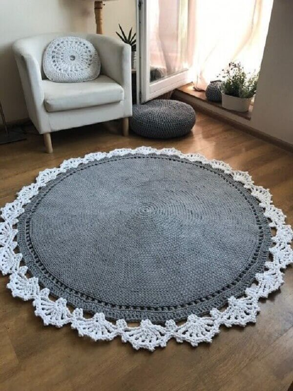 Living room with armchair and round crochet rug in white and gray tone
