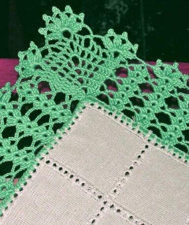Green crochet nozzle on white cloth Photo by By Mariza Crochet