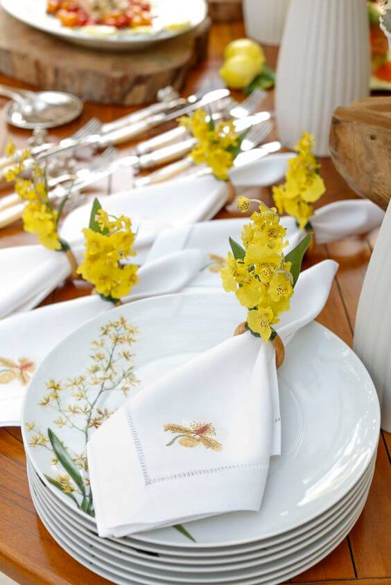 White fabric napkin embroidered with yellow flowers on the ring