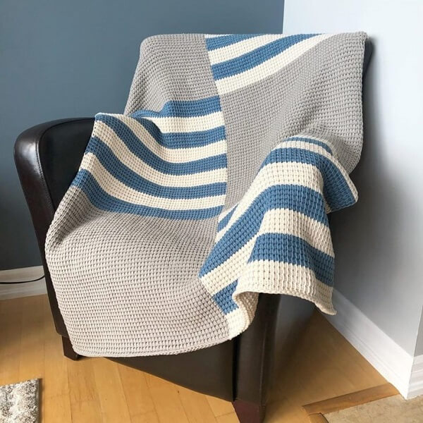 The Tunisian crochet blanket covers the black armchair of the environment