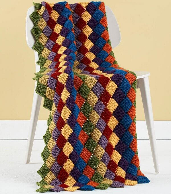 The colorful blanket made in Tunisian crochet brings relaxation to the space