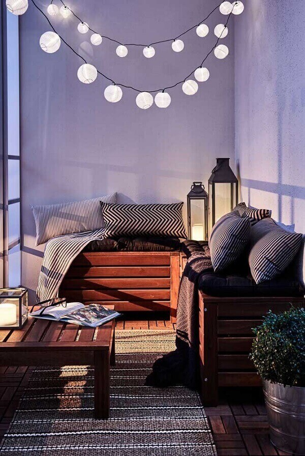Comfortable balcony with bench made of pallet and Moroccan lanterns