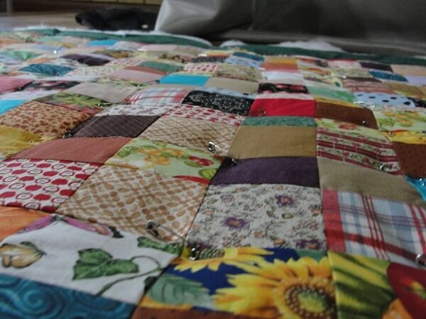 Patchwork quilt on the floor with pins