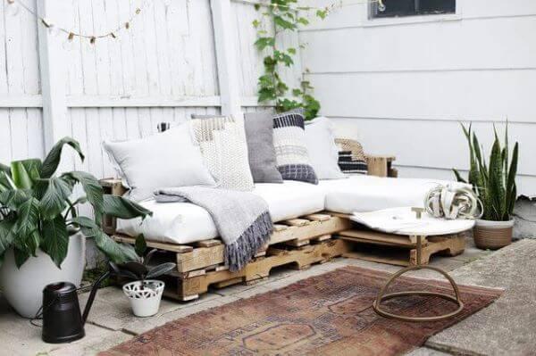 Sofá de palete com almofada e mantinha na varanda