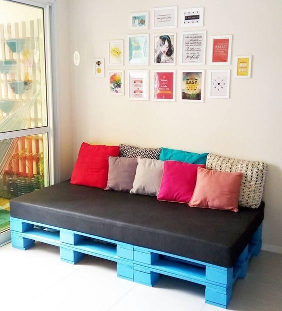 Sofá de palete azul com almofadas rosa