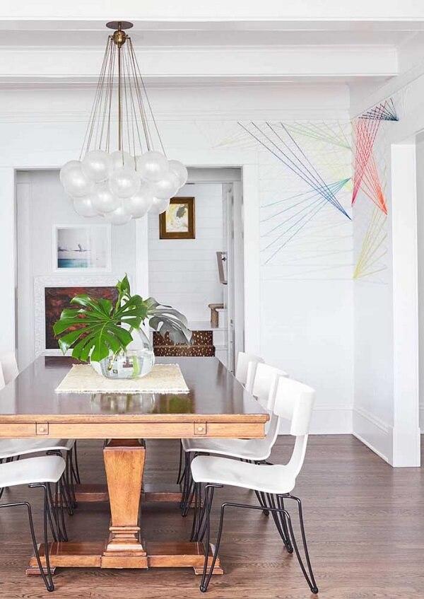 Arte com corda, linhas e pregos se destaca na parede da sala de jantar