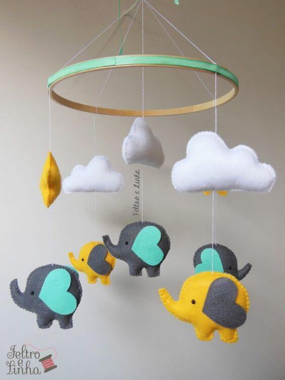 Nuvem de feltro com elefantes no enfeite de quarto de bebê