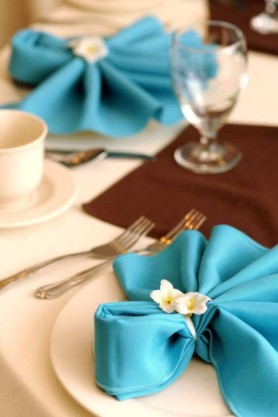 Como dobrar guardanapo de tecido azul com flores decorativas