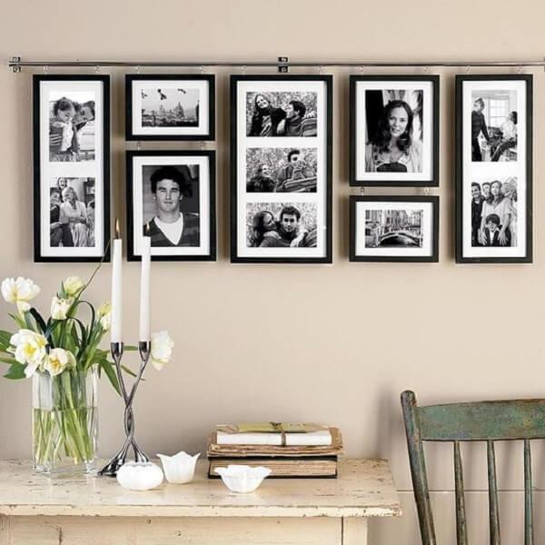 Composição de quadro de fotos pendurados por uma barra metálica